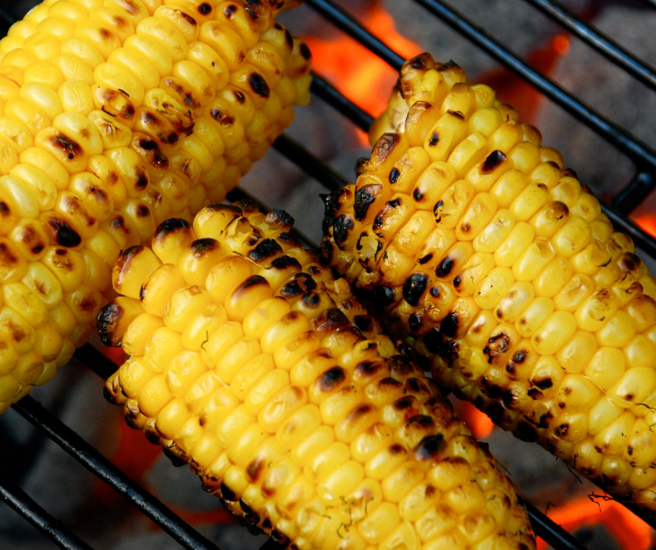 Fresh yellow corn cooking on a grill