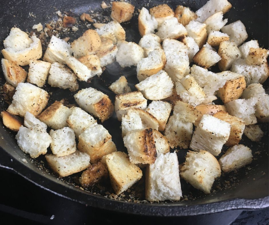 Bread cubes and cooking in an iron skillet