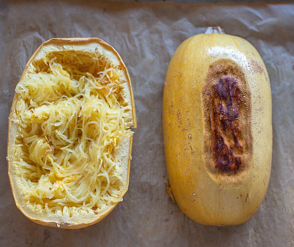 Oven roasted spaghetti squash on a baking sheet. One piece is upside down and the other is right side up