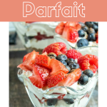 A parfait glass filled with dessert topped with strawberries blueberries and raspberries