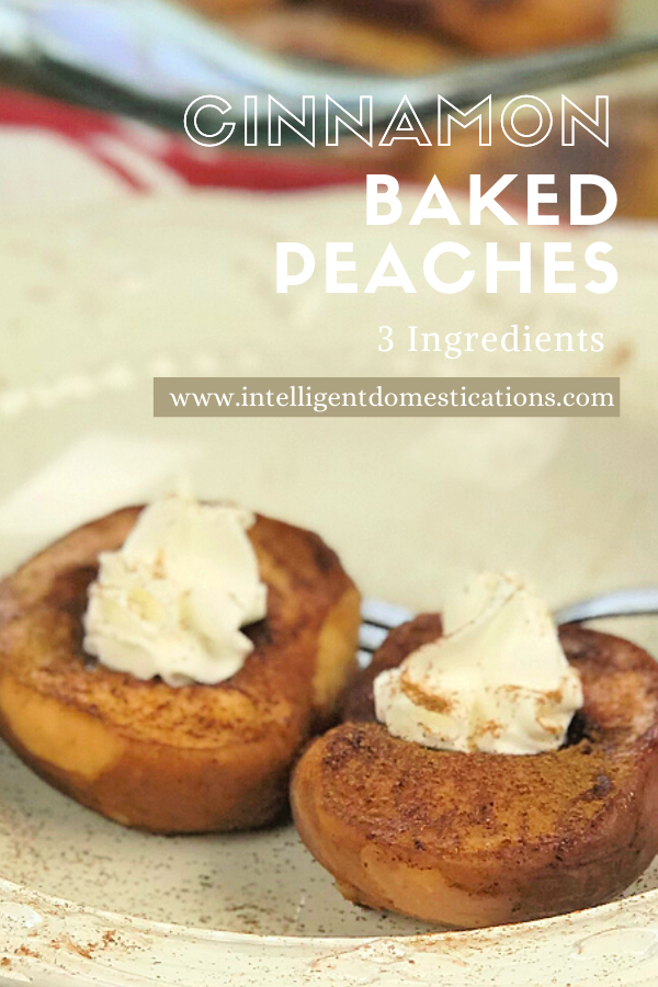 Baked peaches with whipped cream on top sprinkled with cinnamon in a white bowl