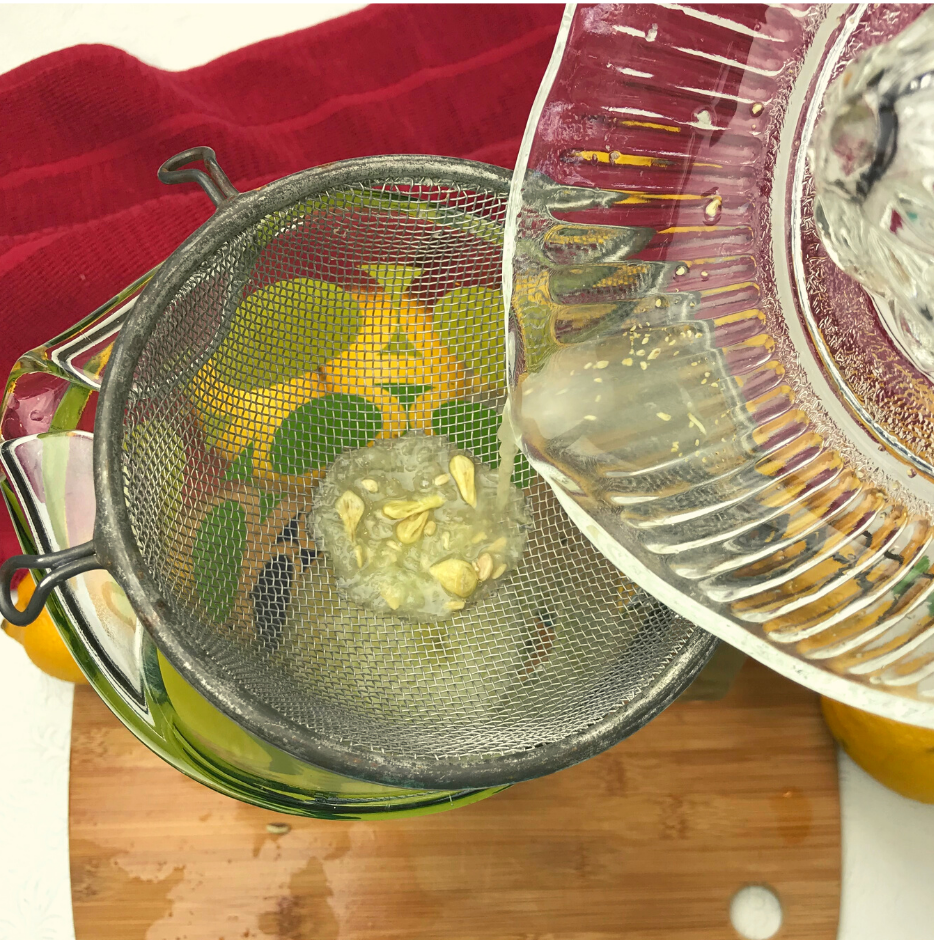 A mesh strainer over a pitcher with lemon juice being poured through it