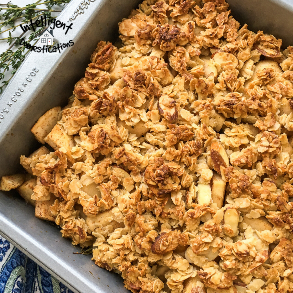 Baked apple crisp with an oat topping in a square metal pan