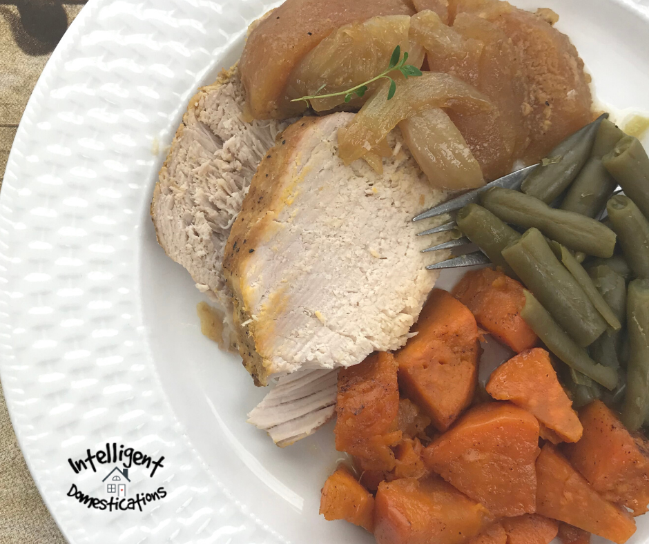Baked pork tenderloin with green beans and candied yams on a white dinner plate