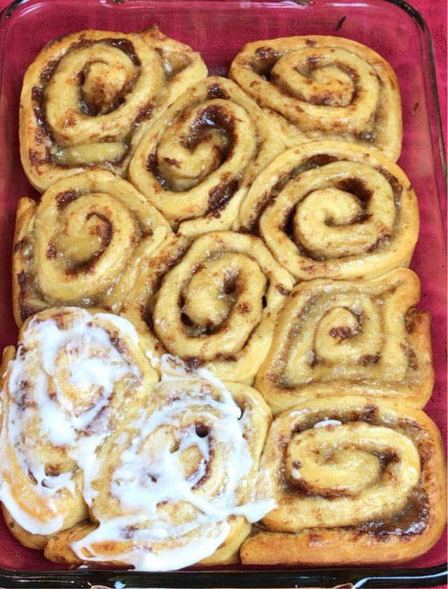 Cinnamon rolls being iced after baking