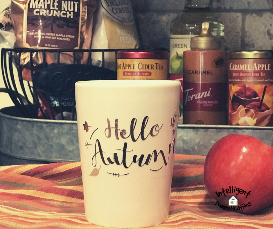 A Fall designed coffee mug sitting in front of hot tea and coffee supplies on a kitchen counter