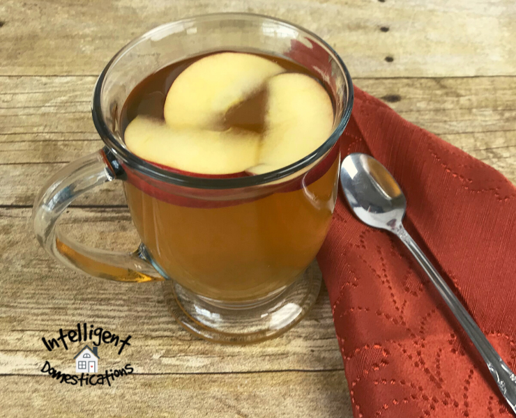 A cup of hot apple cider flavored tea with apple slices floating in it