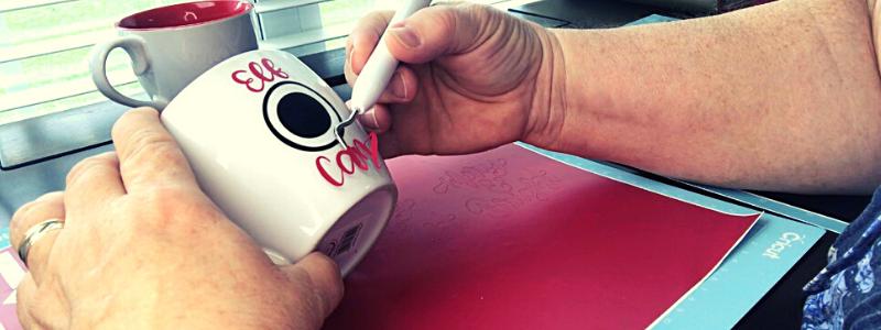 Applying Cricut vinyl lettering to a mug