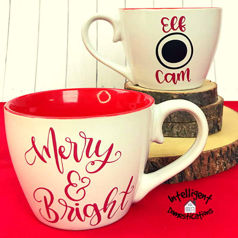Front and back view of a Christmas Elf Cam Mug which is white outside and red inside. It says Merry & Bright