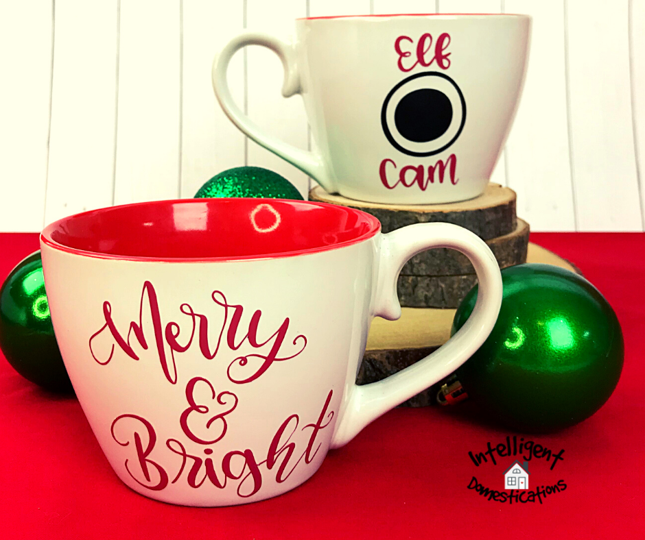 A set of Christmas Elf Cam Mugs displayed on a red cloth with green ornaments