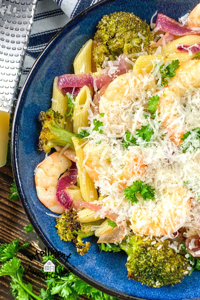 Shrimp pasta and broccoli in a blue bowl with parmesan cheese on top