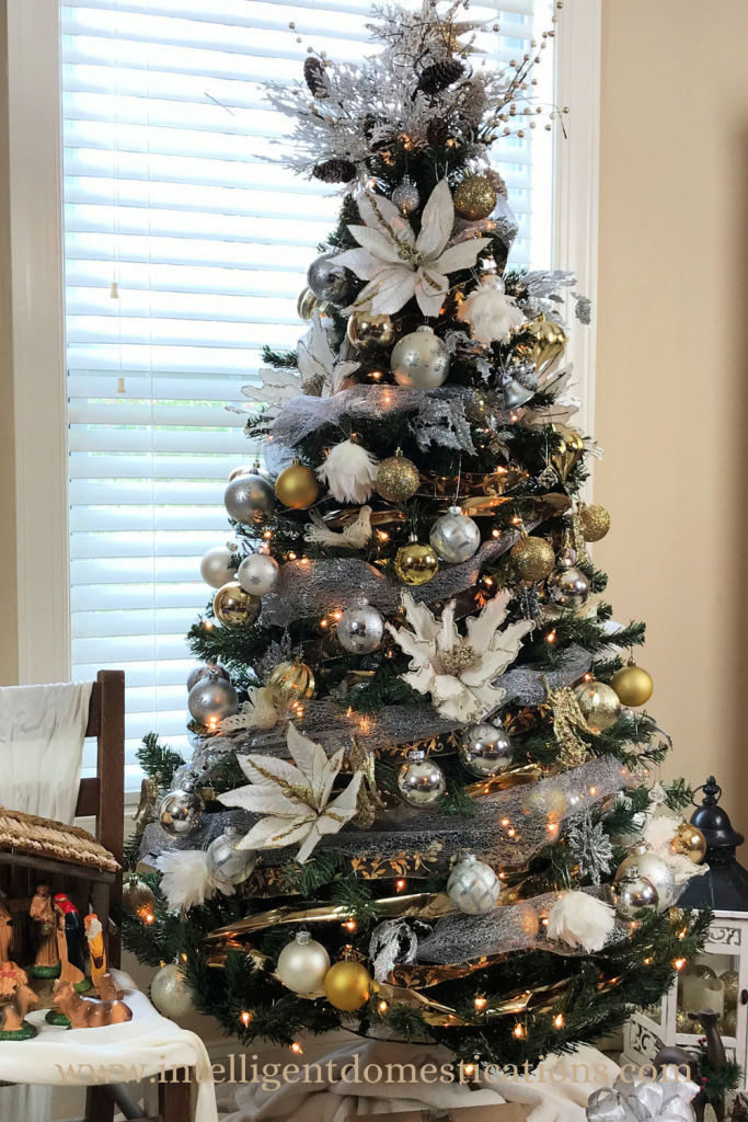 A Christmas tree decorated in silver, gold and white ornaments placed in front of a window.