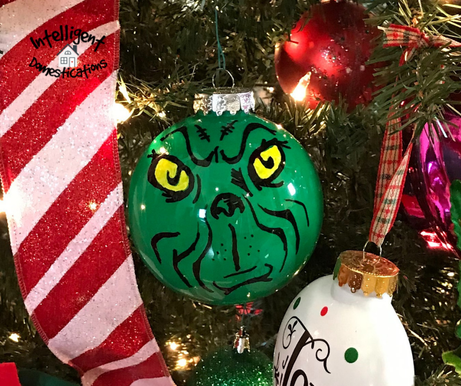 A Grinch ornament hanging on a Christmas tree