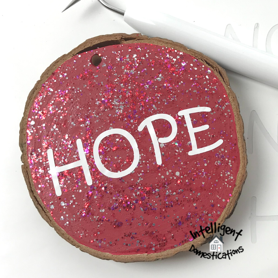 The word HOPE on a red wood slice ornament