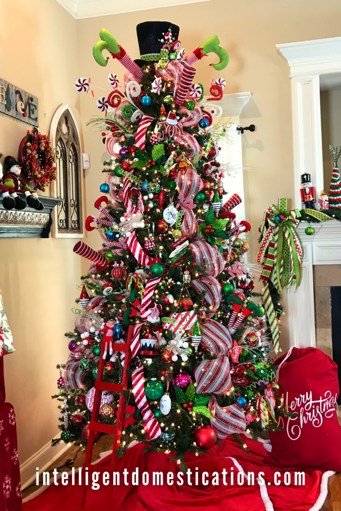 A Christmas tree decorated in an Elf Theme with lots of bright colored ornaments and red and white striped ribbon