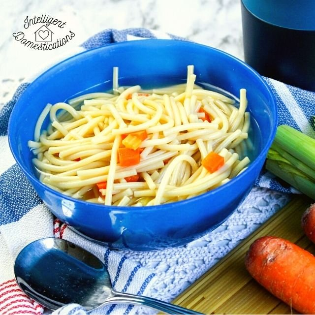 a blue bowl filled homemade chicken noodle soup with carrots and celery next to it