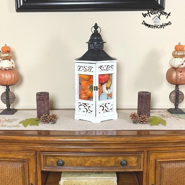 Fall decorations on an entryway console table at the front door