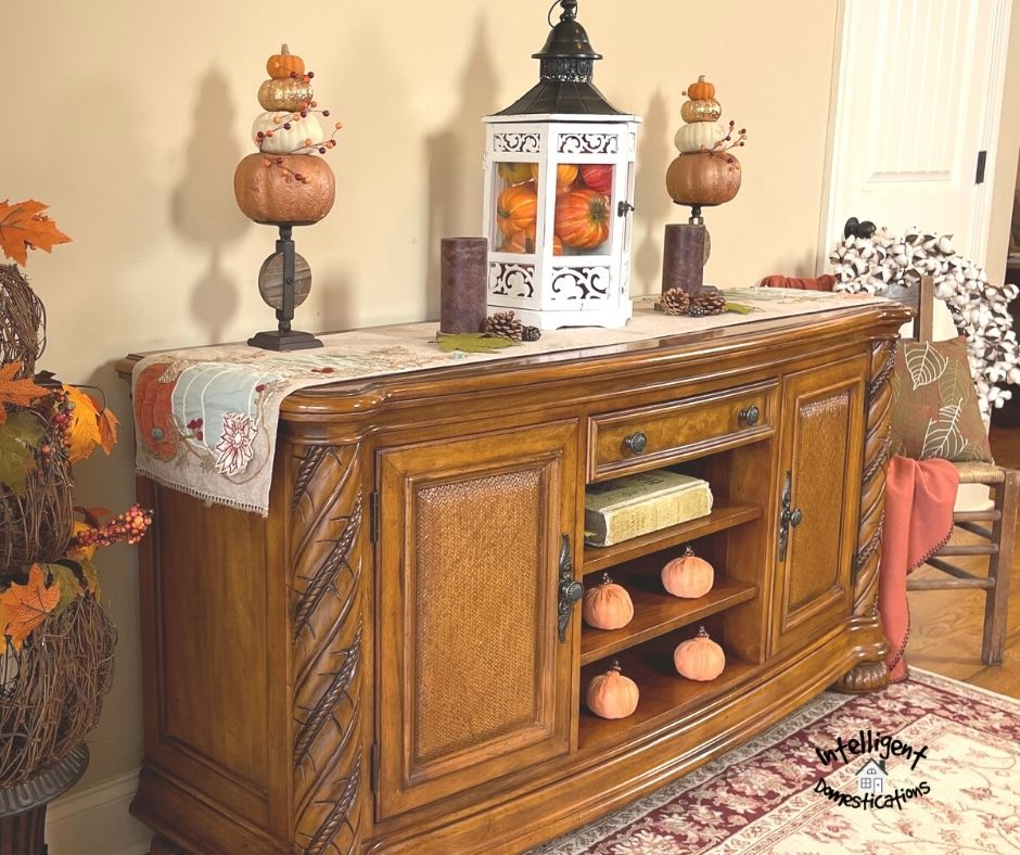 a console table decorated with pumpkins and pine cones in fall colors