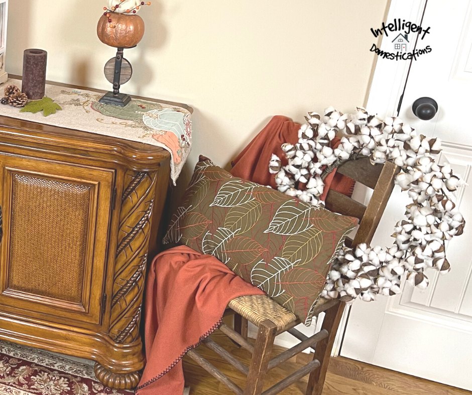 Vintage chair decorated for fall in the entryway next to console table