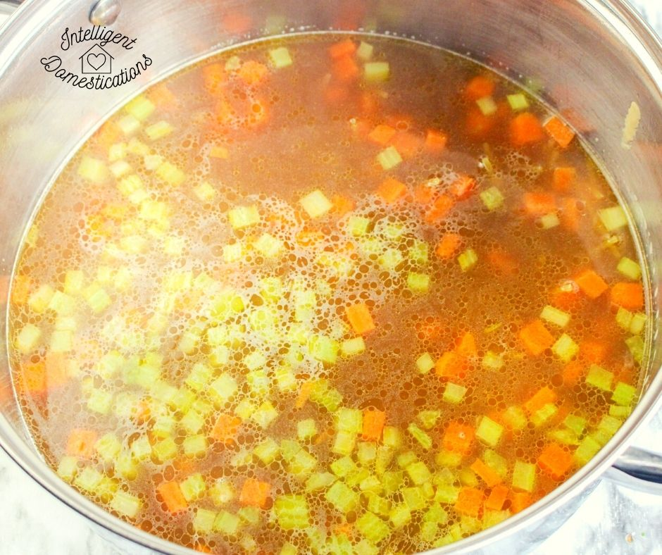 chicken noodle soup base with carrots, celery and chicken stock in a large pot